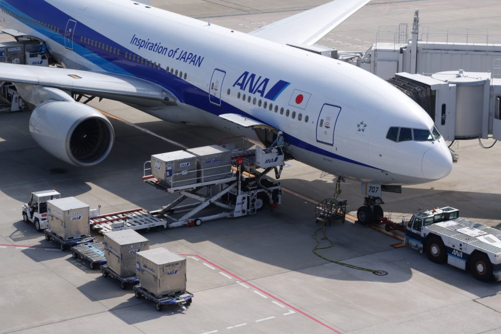Pods being loaded into an ANA 777-200. Look for the two ground power cables by the nosewheel.