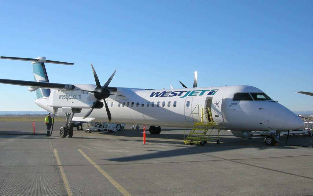 Westjet Encore Bombardier Q400 C-FENY at North Peace Regional Airport (YXJ) in Ft. St. John BC, under a beautiful blue sky.